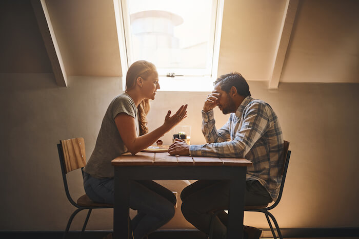 homme et femme assis à table discutant des effets de la violence psychologique