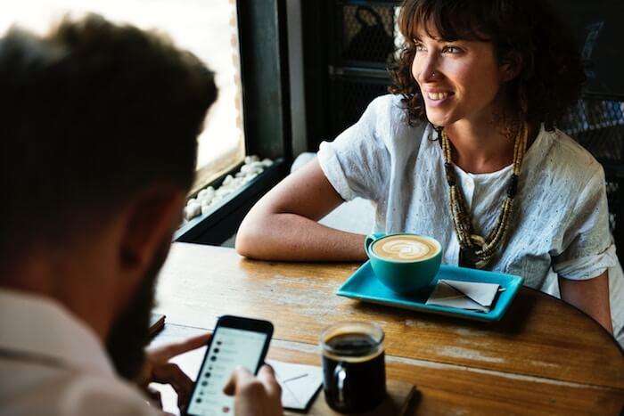 homme envoyant des messages texte à une femme à la table des médias sociaux et des relations