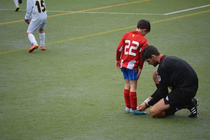 l'arbitre aide un jeune joueur à devenir plus gentil