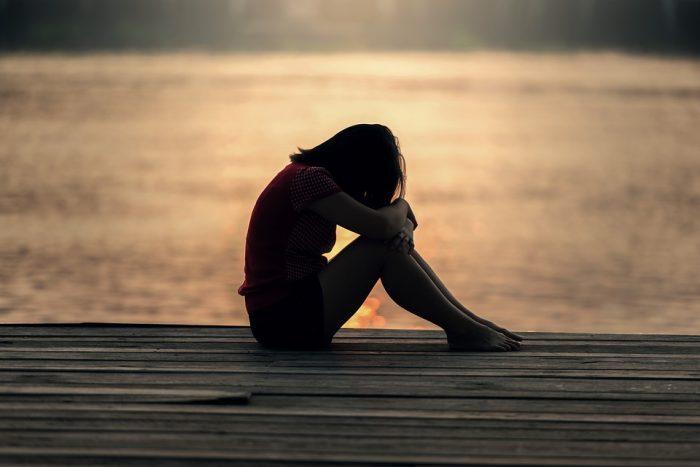 femme assise avec coucher de soleil sur fond de chantage émotionnel