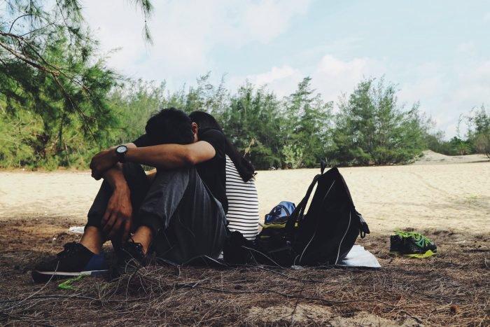 couple ne se parlant pas en étant assis sur le sol en tombant amoureux