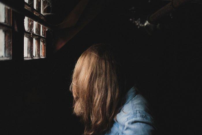 une femme qui tourne la tête sur le côté en se couvrant le visage avec ses cheveux pourquoi les gens sont-ils si méchants
