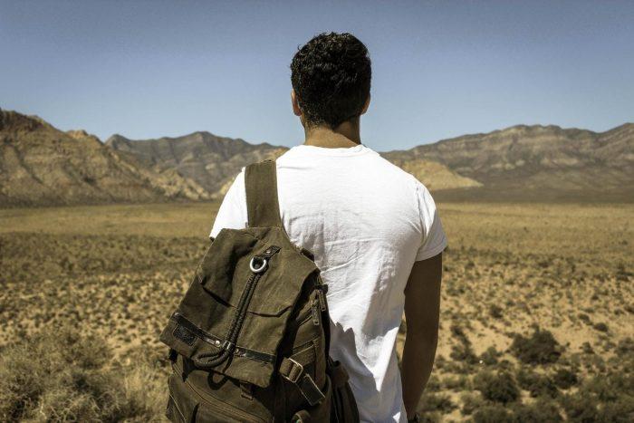 homme portant un sac à dos en regardant un champ et des montagnes qui se sentent perdus