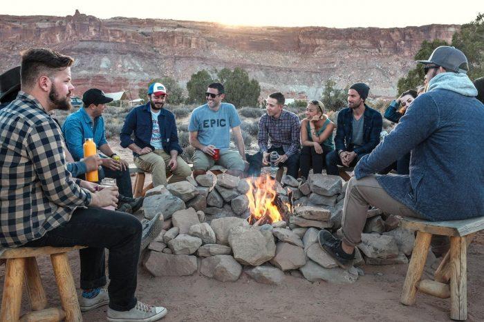 un groupe de personnes se rassemblent autour d'un feu de camp pour poser des questions
