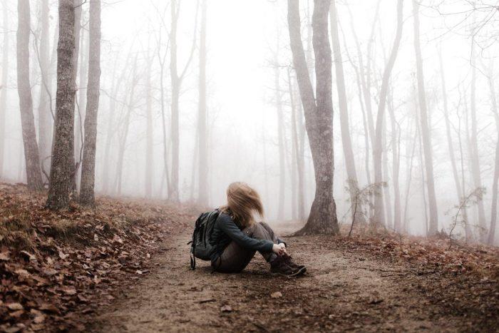 femme assise sur le sol au milieu d'une forêt se sentant perdue