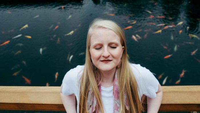 femme aux yeux fermés avec lac et poissons derrière elle comment faire face à la jalousie