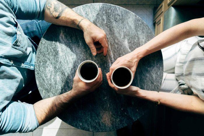 un homme et une femme tenant une tasse de café avec leurs mains sur le dessus d'une table ronde