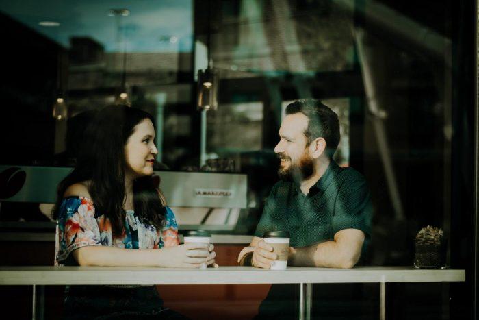 un homme et une femme se parlant tout en tenant une tasse de café