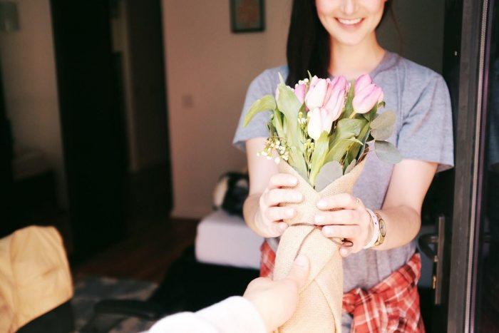 un homme qui offre à une femme un bouquet de fleurs signe qu'il vous aime