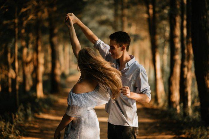 un homme qui danse avec une femme à l'extérieur des enseignes qu'il aime