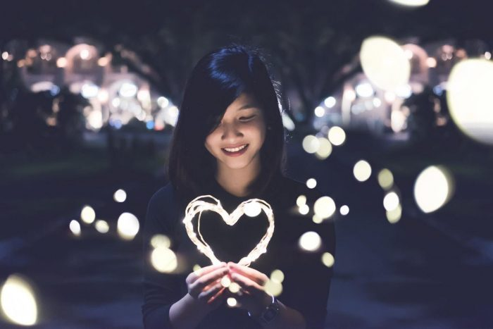femme tenant un fil incandescent en forme de coeur romantique