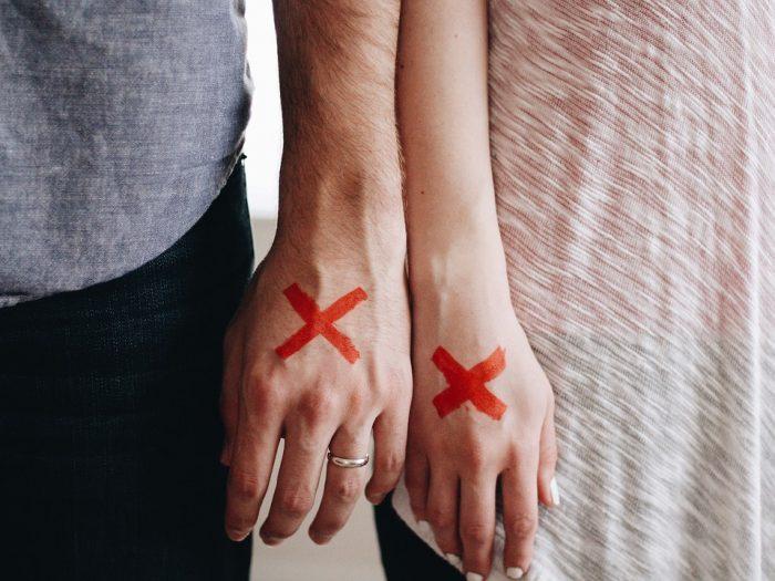 main d'homme et main de femme avec une marque x qui prennent une pause dans une relation