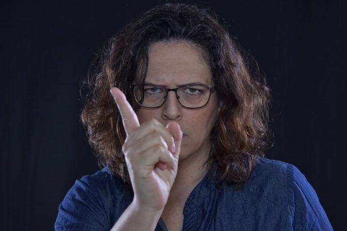 une femme remue le doigt devant une caméra qui contrôle ses parents