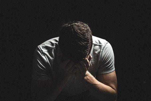 homme portant une chemise blanche lui couvrant le visage avec sa main problèmes de confiance