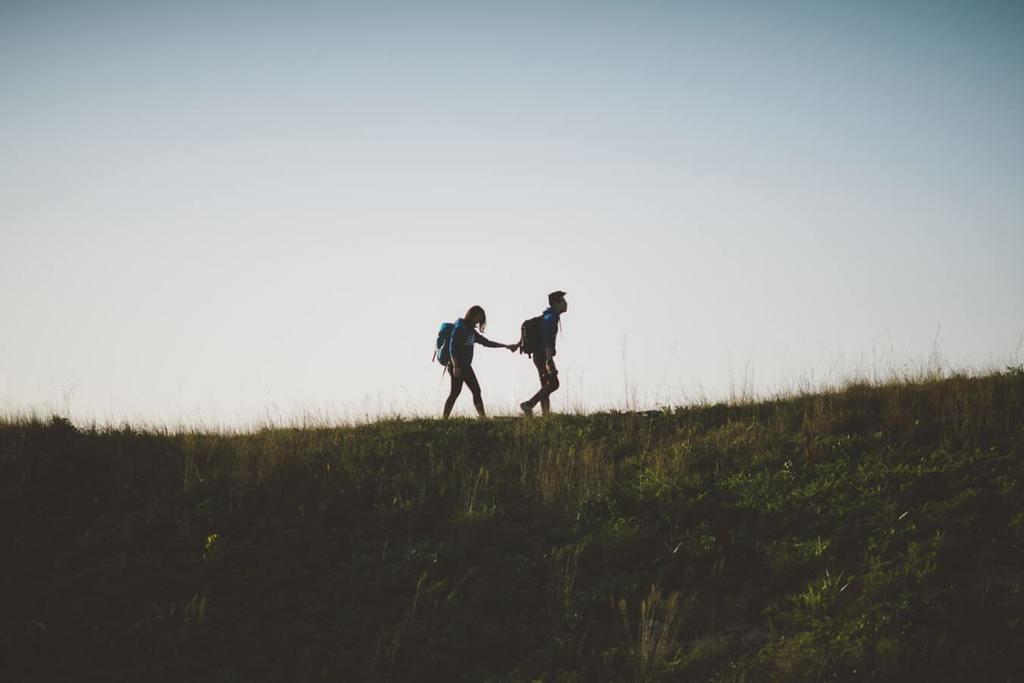 un homme tient la main d'une femme tout en montrant comment surmonter les problèmes de confiance