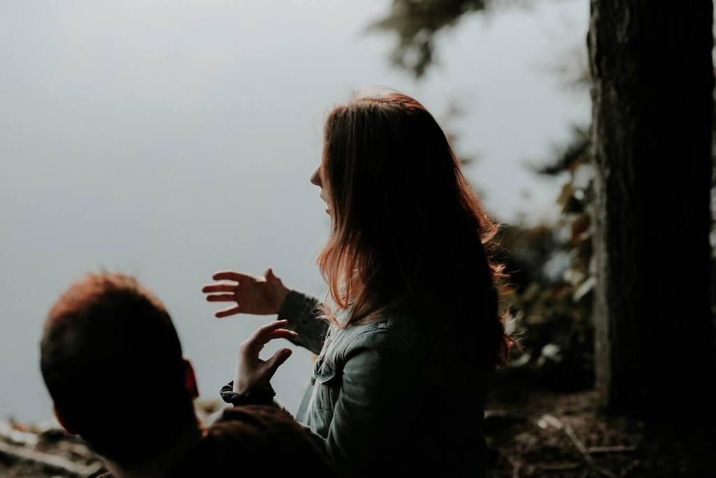 femme expliquant à un homme près d'un lac comment refaire confiance à quelqu'un
