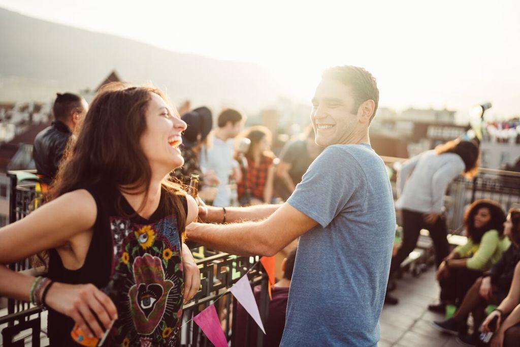 homme et femme riant ensemble devant les signes d'attraction