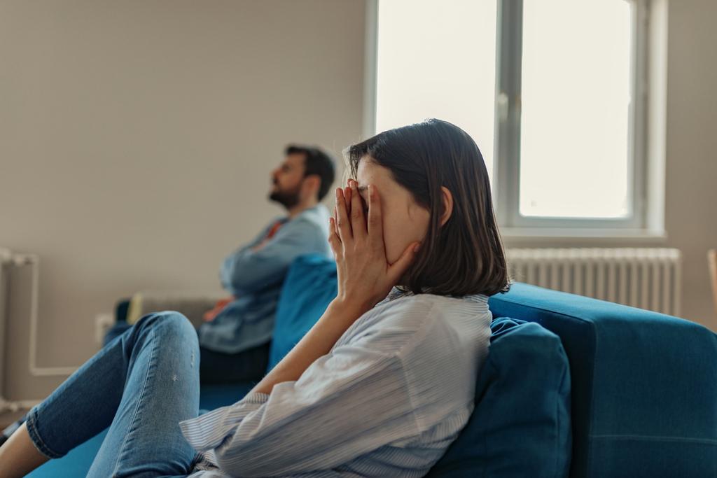 femme sur le canapé se couvrant le visage avec sa main tandis que l'homme s'éloigne d'elle en croisant les bras pour sauver une relation