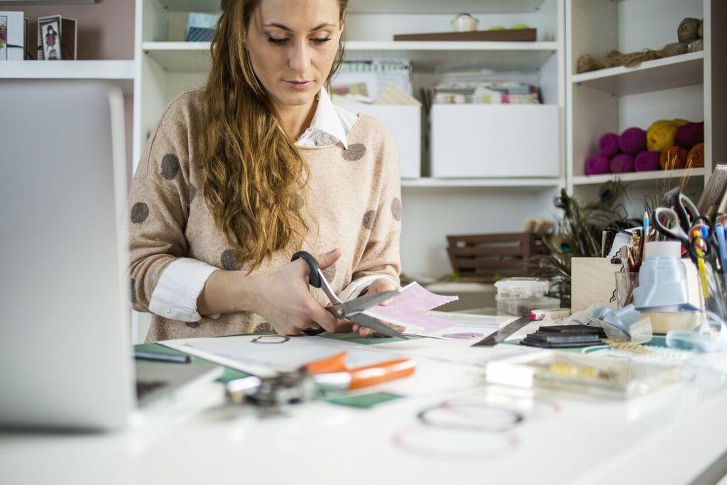 femme coupant un morceau de papier pour faire un tableau de vision