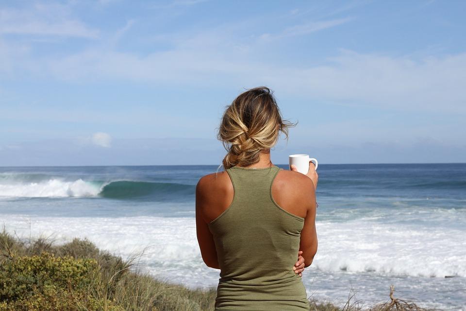 femme tenant une tasse face à l'océan comment affronter un conjoint infidèle
