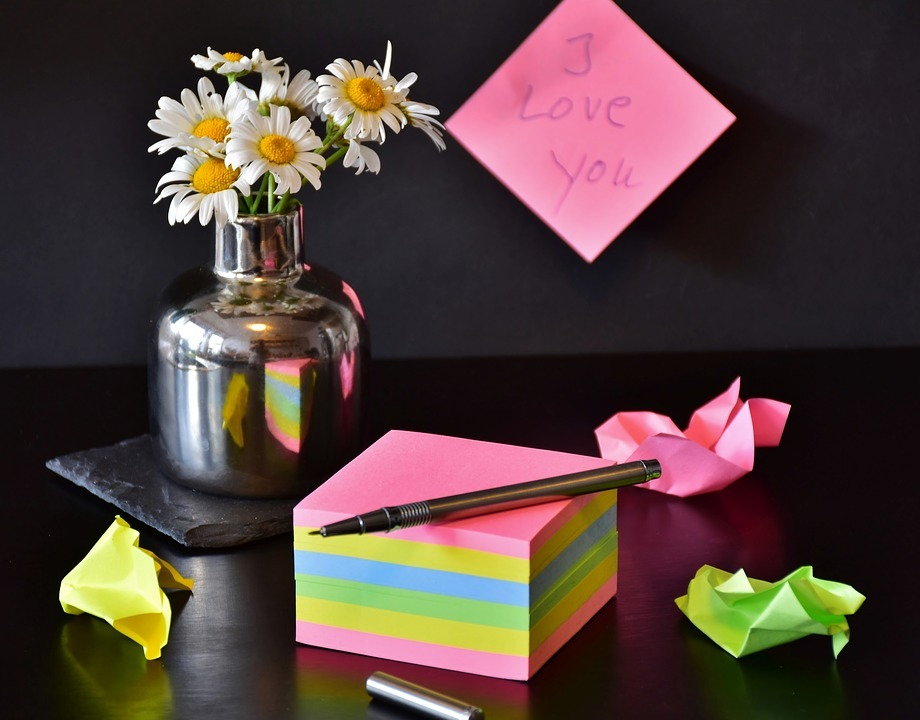 une base de fleurs, des notes autocollantes avec un stylo sur le dessus et une note disant