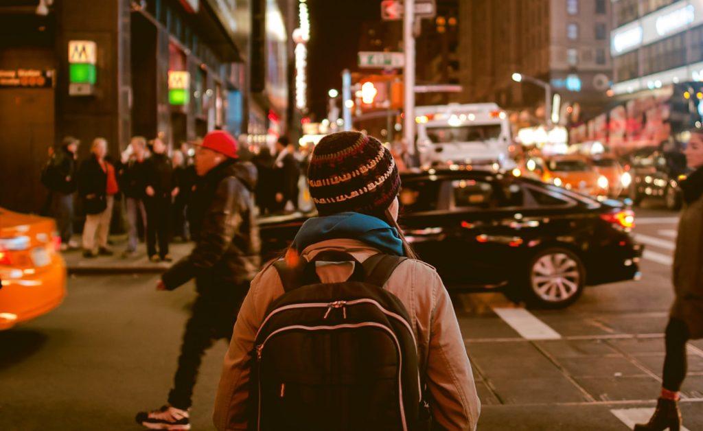 femme portant un sac à dos dans une rue très fréquentée la nuit : que fais-je de ma vie ?