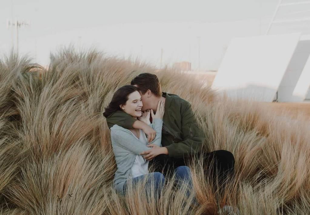 couple assis sur le sol entouré d'herbes hautes préféreriez-vous des questions pour couple