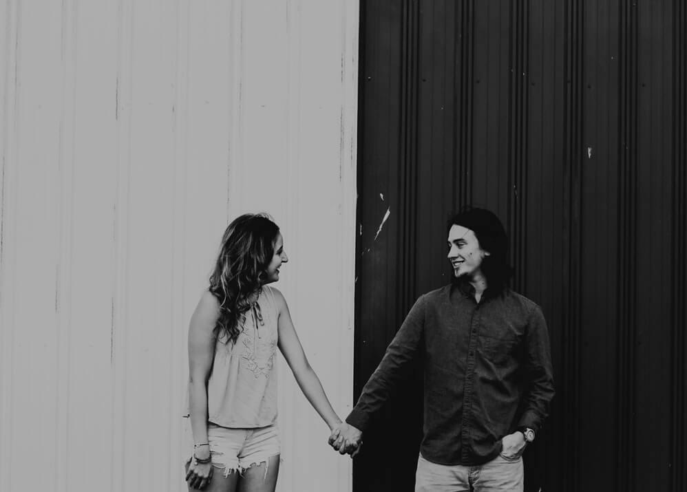 photo en niveaux de gris d'un couple se tenant par la main préféreriez-vous des questions pour le couple