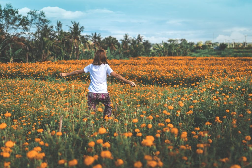 femme dans un champ de fleurs qu'est-ce que je fais de ma vie ?