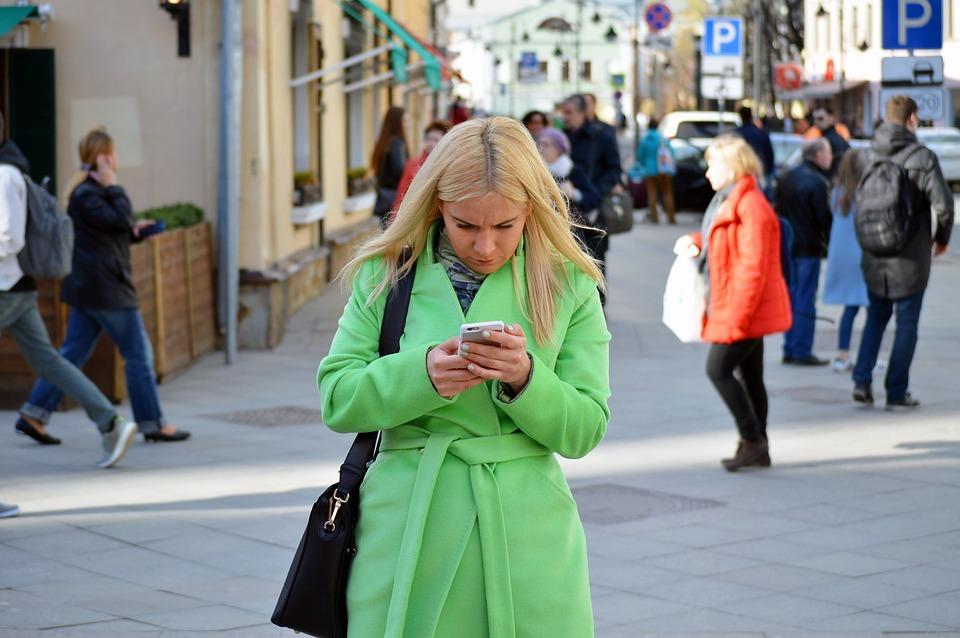 femme en manteau vert dehors regardant son téléphone comment affronter un conjoint infidèle