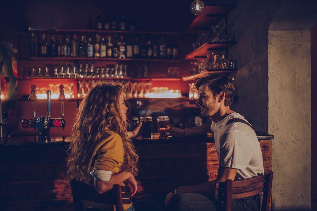 couple parlant à l'intérieur d'un bar tout en buvant de la bière signes d'attraction