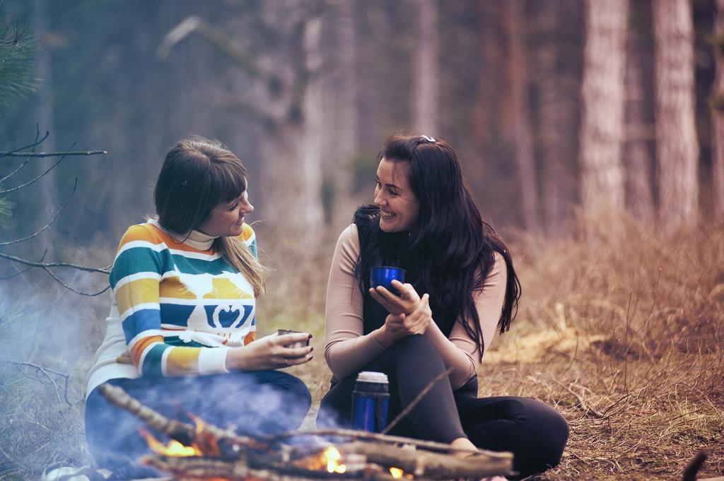 des femmes qui se parlent près d'un feu de joie des questions profondes pour apprendre à se connaître et à connaître les autres