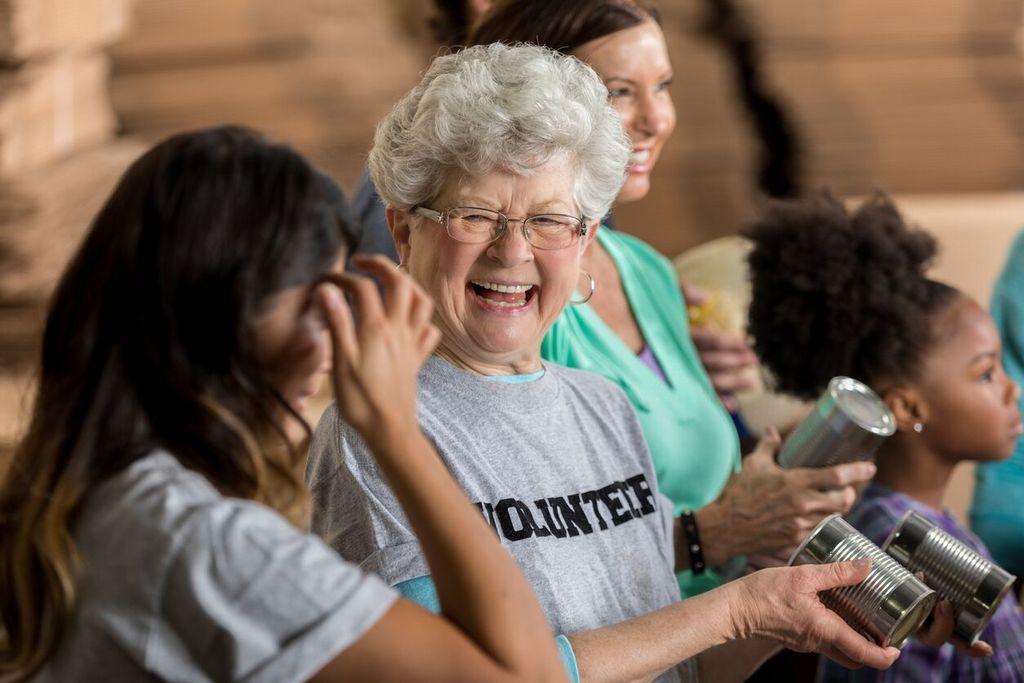 femme plus âgée riant avec une femme plus jeune en tenant des conserves comment recommencer à 50