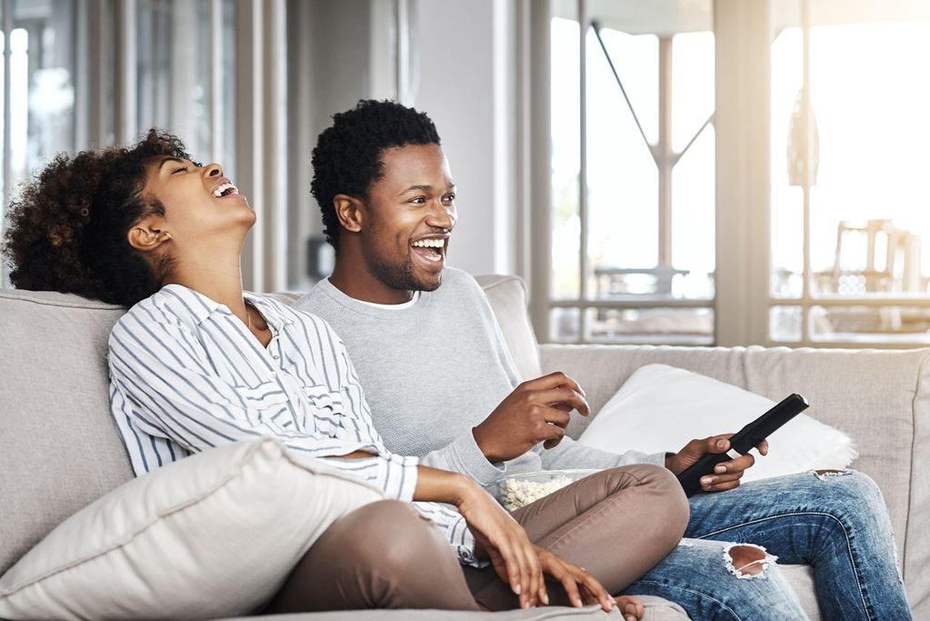 couple riant assis sur le canapé questions intimes pour les couples