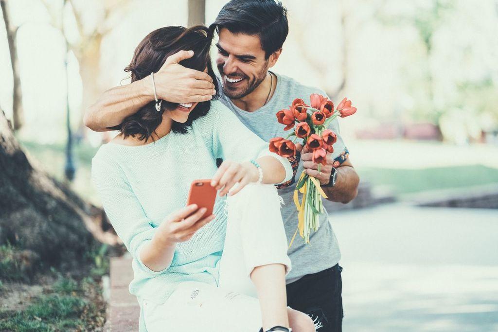 un homme tenant des fleurs d'une main et couvrant les yeux de la femme de l'autre dit