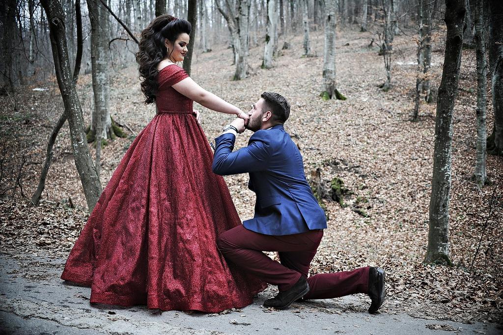 homme à genoux en embrassant la main de la femme gestes romantiques