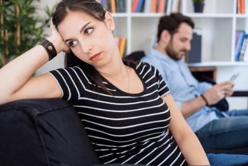Femme ignorant l'homme tandis que l'homme occupé sur son téléphone moyens de faire face à un mari irrespectueux