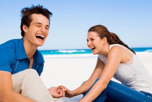 Couple en riant à la plage des questions drôles à poser à une fille