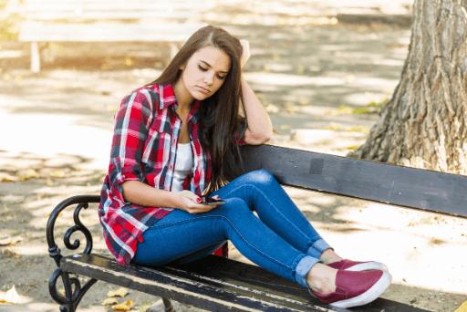 Femme assise sur un banc à l'extérieur en regardant son téléphone arrêter d'aimer quelqu'un qui ne t'aime pas