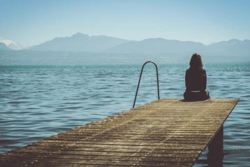 femme assise seule près du lac raisons pour lesquelles vous êtes toujours célibataire