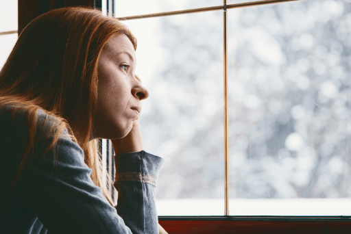 Femme regardant à l'extérieur par la fenêtre des raisons pour lesquelles vous êtes toujours célibataire