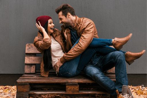 Couple jouant assis sur un banc en bois qualités d'un homme bon